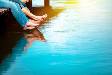 Romantic couple man and woman are sitting on a dock with barefoot feet dangling in pond water. Sunny weather. Happiness, vacation, summer, concept. Copy space for text. Wall mural