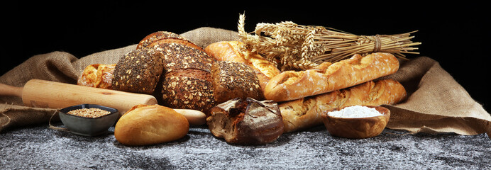 Zelfklevend Fotobehang Bakkerij Assortment of baked bread and bread rolls on rustic grey bakery table background