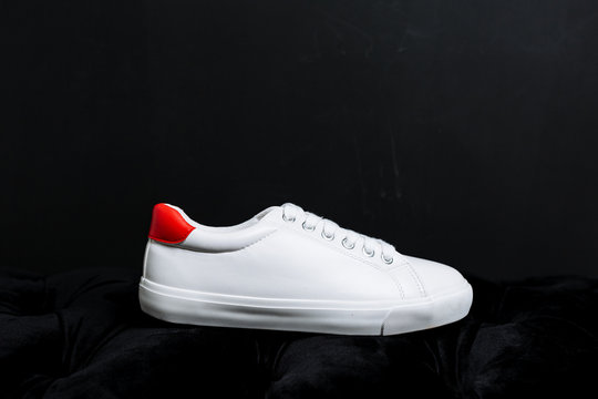white sneakers with a red back on a dark background