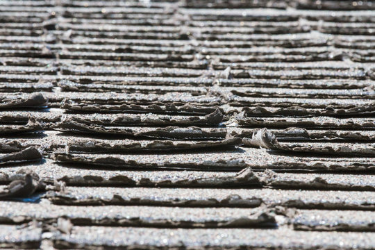 Worn-out asphalt shingles on a roof; shingles needing replacement or repair