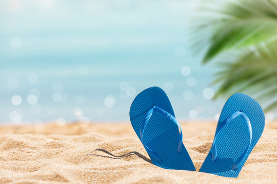 flip flops on the sunny tropical beach with palm trees and turquoise water, Caribbean island vacation, hot summer day
