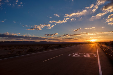 Route 66 pavement sign in the foreground and the diminishing perspective of the road leading to a dramatic sunset in the Mojave desert outside of Amboy, California.