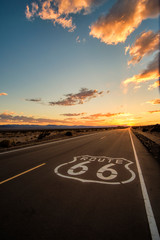 The wide open road of route 66 leading towards a dramatic sunsets over the horizon in the Mojave Dessert just outside of Amboy, California.