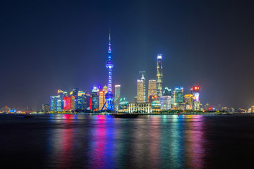 The Pearl in Shanghai Downtown skyline by Huangpu River, China. Financial district and business centers in smart city in Asia. Skyscraper and high-rise buildings near The Bund at night.