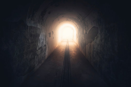 Light in end of tunnel. Long underground concrete corridor in abandoned bunker, toned