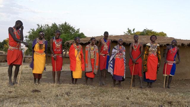 wide view of a group of ten maasai women and men singing