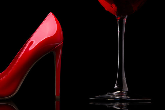 A glass of red wine and women's shoes with heels. Red high-heeled shoes and a glass of wine.