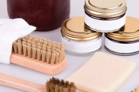 Cream, brushes and napkin for the care of shoes. Shoe care products. Shoe cosmetics close-up.