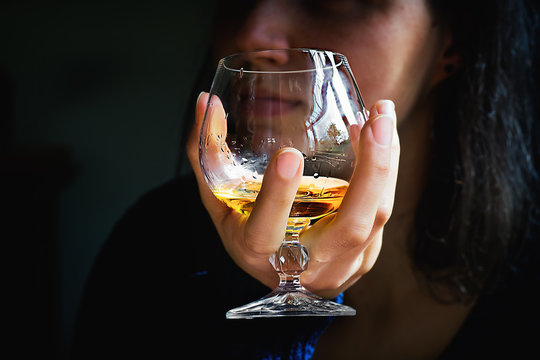Woman's hand with glass of alcohol drink
