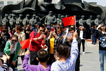 Chinese visitors take pictures near statues of soldiers who took part in the Korean War, by the Yalu river in Dandong