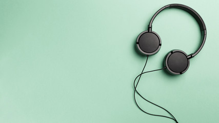 Black headphones on Mint background. Headphones on a pastel background. Flat lay top view copy...