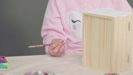 Wall Mural - Little girl painting a white unicorn with acrylic paint on a wooden box.