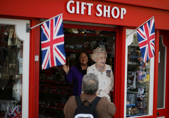 A woman poses for a photograph next to a cardboard figure of Britain's Queen Elizabeth in a gift shop in Windsor