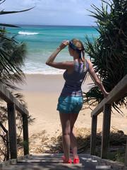 Femme tenant ses lunettes de soleil sur un escalier menant à la plage
