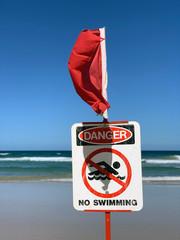 Drapeau rouge et panneau de baignade interdire