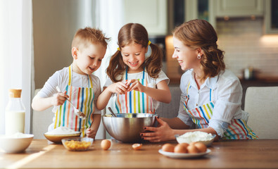 happy family in kitchen. mother and children preparing dough, bake cookies.