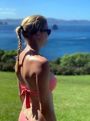 Jeune femme portant une tresse et un bikini rose devant des pelouses et une mer turquoise