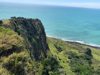 Bord de mer turquoise bordée de pelouses derrière un rocher
