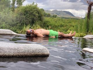 Jeune homme couché et détendu entre des eaux calmes et la nature