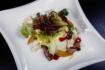 Appetizing salad sliced with pear slices of prosciutto pear arugula and parmesan
