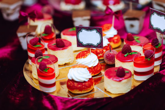 chic desserts on the tray are decorated with raspberries. weddin