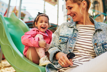 Candid image of happy young woman laughing with her little cute daughter spending time together outdoors on slide at playground. Mother with her toddler girl feeling happy, loving each other outside.