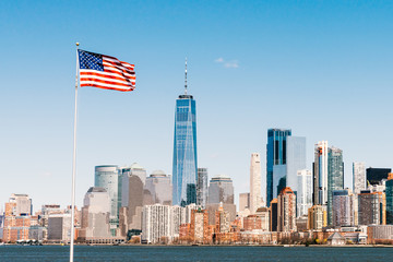 American national flag on sunny day with New York city Manhattan island in background. America cityscape, or United States nation symbol concept