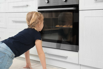 Little girl waiting for preparation of cookies in oven at home