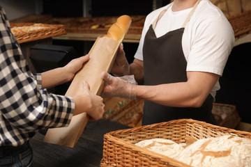Woman buying fresh baguette in bakery shop, closeup