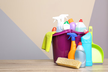 Bucket with cleaning supplies on wooden table against color background. Space for text