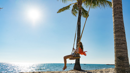 Vacation concept. Young woman swing on a beach swing. Happy traveller women on the Phu Quoc beach Fototapete