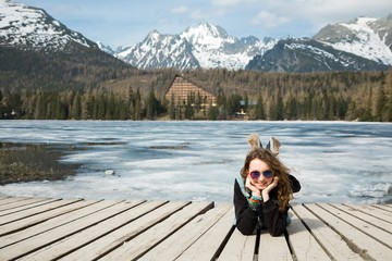 Young girl is lying on wooden terrace by frozen mountains lake S