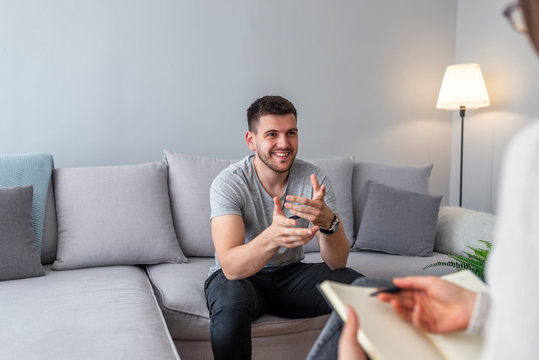 Psychologist talking with happy man in the office. Image of young man during psychological therapy. Female psychologist consulting man during psychological therapy session