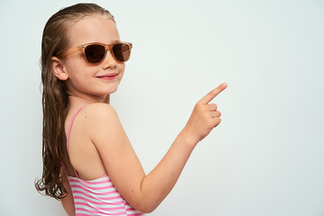 Smiling little preschool girl with wet hair photographed against white background wearing swimsuit and sunglasses pointing up with finger towards empty space