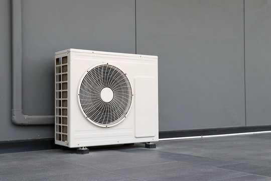 Condensing unit of air conditioning systems. Condensing unit installed on the gray wall.