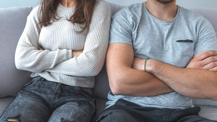Close up of a couple arguing with the arms crossed. Young couple sitting on the sofa after quarrel. Couple sitting on the couch not speaking after a fight at home in the living room
