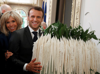 French President Emmanuel Macron and his wife Brigitte pose next to a bouquet of Lily of the Valley flowers during the annual May Day ceremony during which French food products are displayed at the Elysee Palace, in Paris