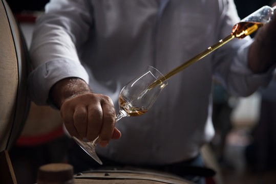 Man, pouring cognac from the barrel into glass in old rustic underground wine cellar with rows of big oak barrels. Famous wine and brandy industrial destination