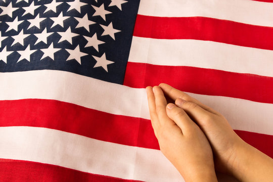 Hands of praying little girl on the background of the American flag. The concept of patriotism.