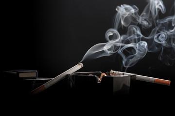Closeup of cigarette on ashtray with a beautiful wisp of smoke
