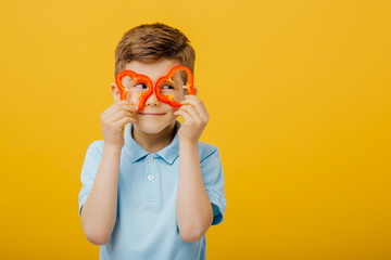little boy glasses pepper slices, in blue T-shirt, isolated yellow background, copy space