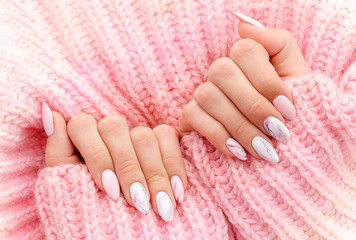 Foto op Canvas Manicure Female hands manicure close up view on pink knitted sweater background. Nail painting effects. Manicure salon banner concept