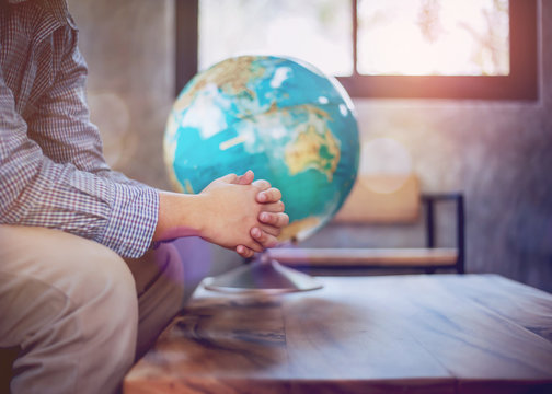 A young man sit on  wooden chair while praying to God over blurred world globe on wood table in door against window light,  great mission or world save concept with copy space.