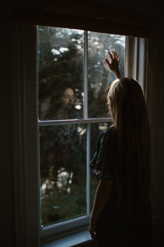 sad woman looking out window in home