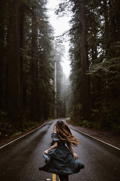 woman in blue dress on road in forest redwoods