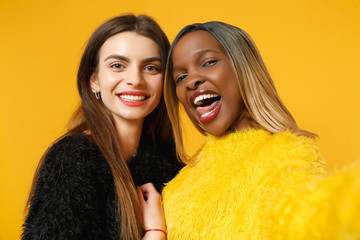 Two women friends european and african american in black yellow clothes doing selfie shot posing isolated on bright orange wall background studio portrait. People lifestyle concept. Mock up copy space