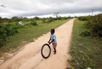 A child plays on a road as storm clouds gather in the aftermath of Cyclone Kenneth on Ibo island north of Pemba, Mozambique