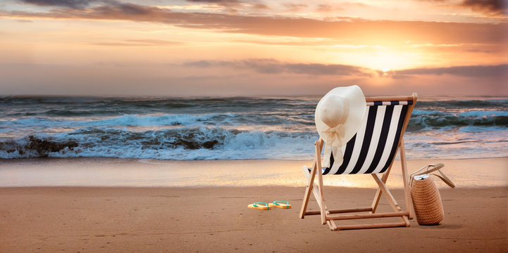 Beach chair with hat on tropic beach