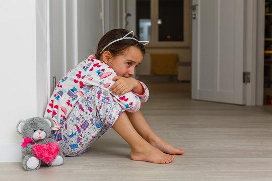 Sad little girl sitting near the wall