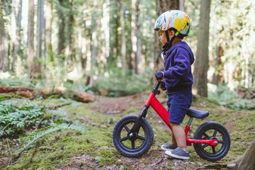 Side view of boy riding bicycle in forest